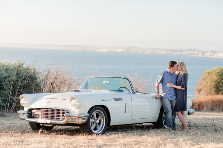couple kissing in front of Ford Thunderbird on cliffs of Palos Verdes