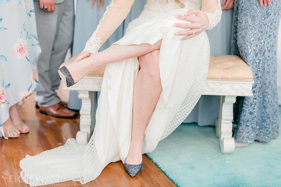 bride putting on wedding shoes
